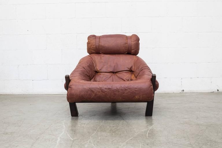 Gerard Van Den Berg lounge chair for Montis, 1970-1972. Tobacco colored leather with visible patina and heavy tripod base frame. Smart tension strap support system. Original condition.