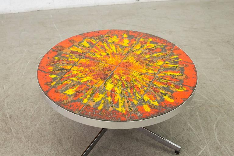 Artistic round tiled coffee table with custom red, orange, yellow, green molten lava tilework. Aluminium edge and chrome pedestal base in original condition. Visible wear consistent to its age and usage.
