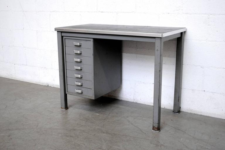 Minimalist Industrial desk with grey metal frame and original Linoleum top. 7 drawers with brushed chrome hand pulls. Metal horseshoe foot caps.