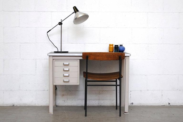 Light grey industrial metal office desk. 4 drawers with brushed chrome hand pulls. Original black linoleum top. In very original condition with wear consistent with its age and usage.