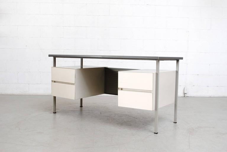 Floating grey vinyl topped Industrial desk with pale grey enameled metal frame and privacy screen with white enameled double drawers. Good original condition with visible wear consistent with its age and usage.