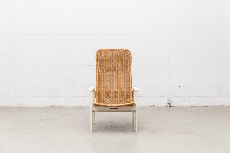 Elegantly woven Dirk Van Sliedregt rattan high back lounge chair with white wood frame and arm rests. Visible signs of wear consistent with its age and usage. Other similar styles available and listed separately.