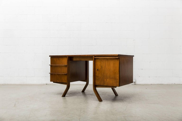 Beautiful Mid-Century oak writing desk designed by Cees Braakman for Pastoe. Left side features three sliding drawers with organically carved hand pulls. Right side features large key-entry storage cabinet with sliding sectional pull out trays.