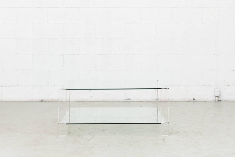Beautiful two-tiered glass coffee table with four clear Lucite legs. Ultra chic, original condition with visible wear to glass and Lucite frame.