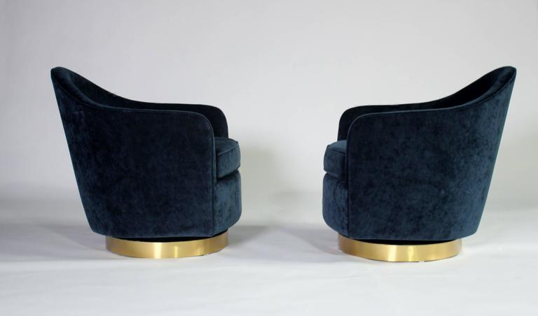 """Pair of 1970s barrel-back, teardrop-shape, tilt and swivel chairs designed by Milo Baughman for Thayer Coggin completely reupholstered and restored in Vanguard """"Indigo Viking"""" blue velvet fabric and brushed brass bases."""