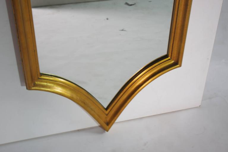 Mid-Century decorative gold giltwood mirror in a unique Hollywood Regency style.