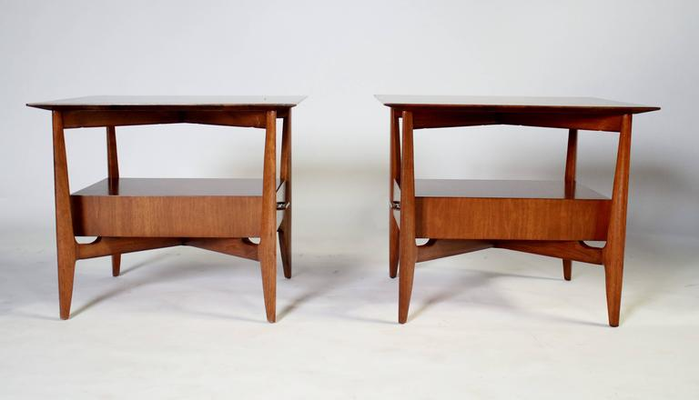 Pair of 1960s sculptural walnut end tables by John Stuart with a floating single drawer and original brass pulls.