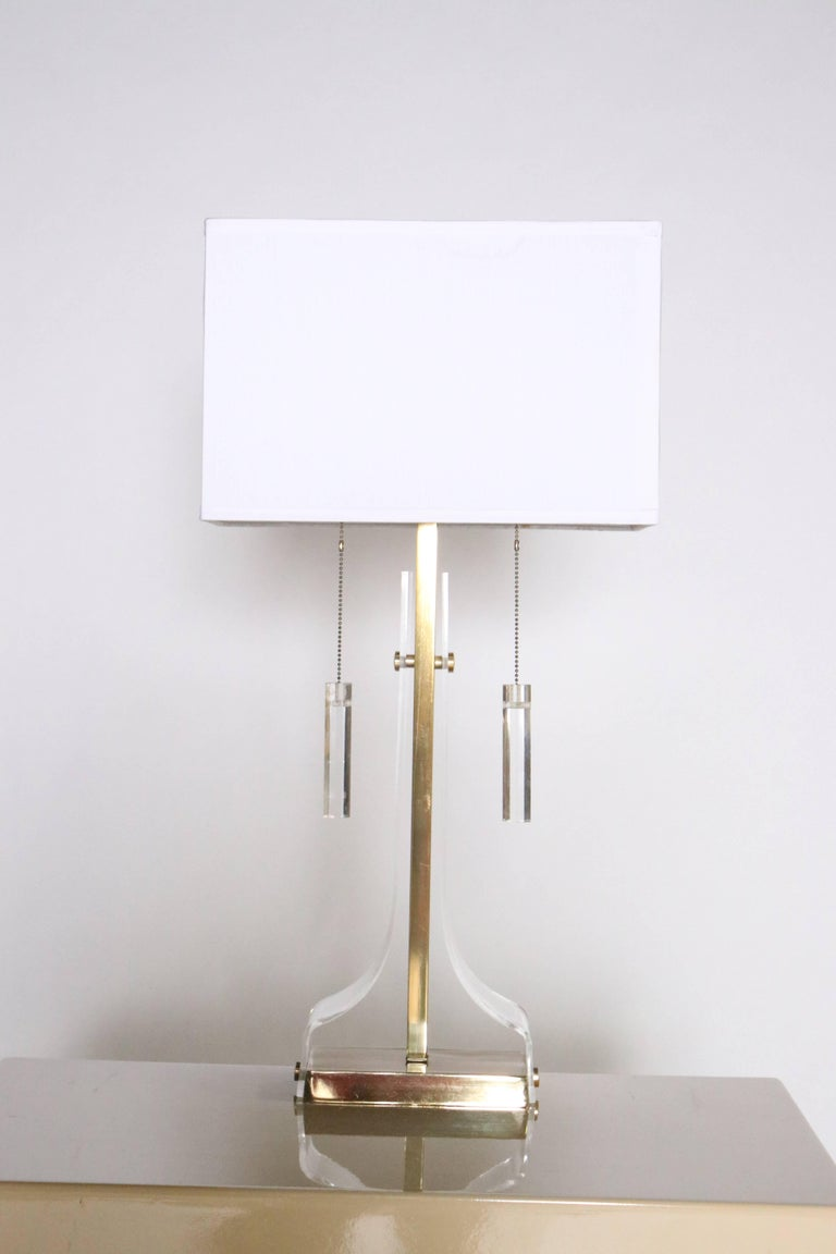 Lucite and brass table lamp by Laurel with Lucite pulls and two-sockets. Shade included.