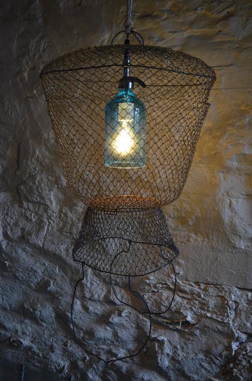 pendant light from seltzer bottle suspended in french steel mesh