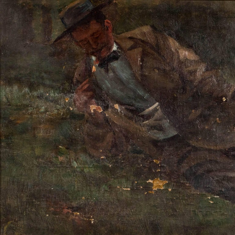 Original oil painting of a Victorian gentleman holding a box of matches and lighting his cigar while reclining in a forest setting. There are areas of age related paint loss scattered across the canvas. The painting is mounted in a gold painted