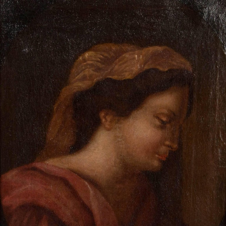 An unsigned late 18th or early 19th century antique oil painting portrait of a woman in robes. The painting is in the style of the Italian school with craquelure throughout the canvas which is mounted in a giltwood frame. The frame has minor scrapes