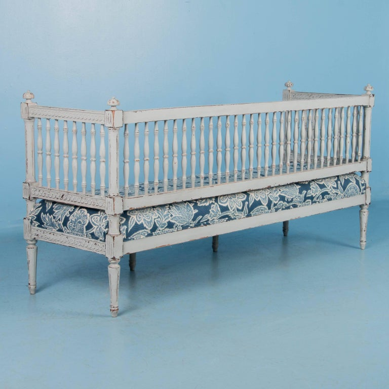 The lovely, soft colors of the Gustavian period are well displayed in this exquisite bench. Where the new light gray painted finish is worn away, the darker natural wood comes through, enhancing the exceptionally carved apron and rails of this