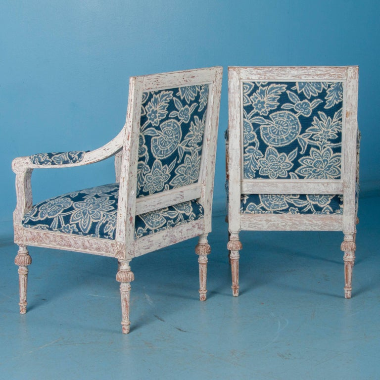 This elegant pair of carved armchairs have a distressed white painted finish that contrasts with the natural wood and hints of red paint beneath, accentuating the Classic lines of the Gustavian period. The hand-carved ribbon and rope patterns around