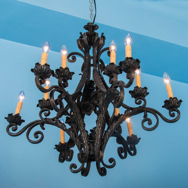 This antique French wrought iron chandelier, circa 1920, has six arms that radiate out from the centre. Each arm is set with a pair of lights, all with a candle cover and resting on a floral drip pan. With scrolled arms and applied leaf details, the