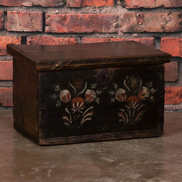The delightful hand-painted floral motif seen on this small trunk or box was a traditional Folk Art style in the 1800s throughout Europe. Accent colors of red, eggshell and green are still seen in the flowers painted on the front panel. The entire