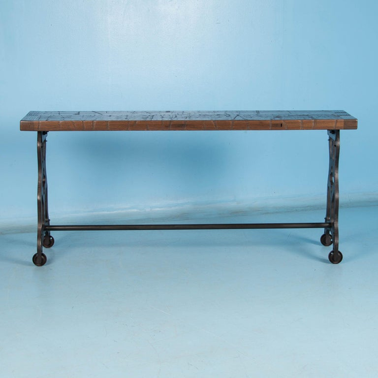 Made in the USA from reclaimed railroad box car flooring, the top is solid vintage oak. This long console table features antique cast iron legs that come from Danish industrial machinery. The rustic top has a durable finish and the iron stretcher