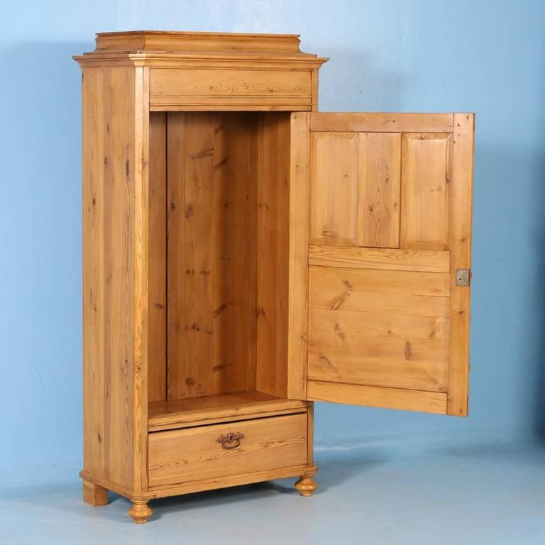 This Danish pine single door armoire is sometimes referred to as a 'false front' as it was designed to look like a two-door cabinet with drawers underneath. The reality is that this is just an