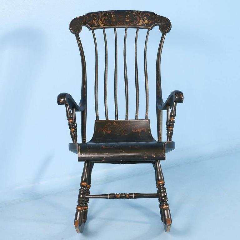 An antique spindle back rocker from Sweden dated 1911, with scrolled arms  and supported by - Antique Black Swedish Rocking Chair With Original Black Paint, Dated