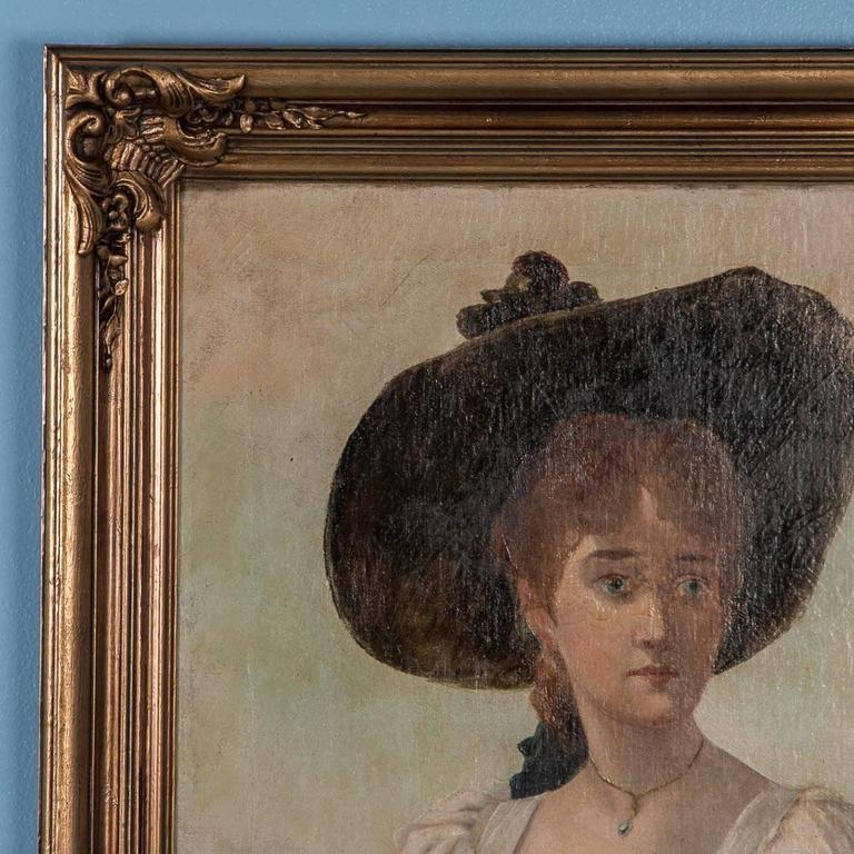 Original oil on canvas painting portrait of a young Victorian English woman wearing a white dress with yellow sash and holding a basket of yellow flowers. The painting is unsigned and mounted in a new gold painted gesso and wood frame. Please take a