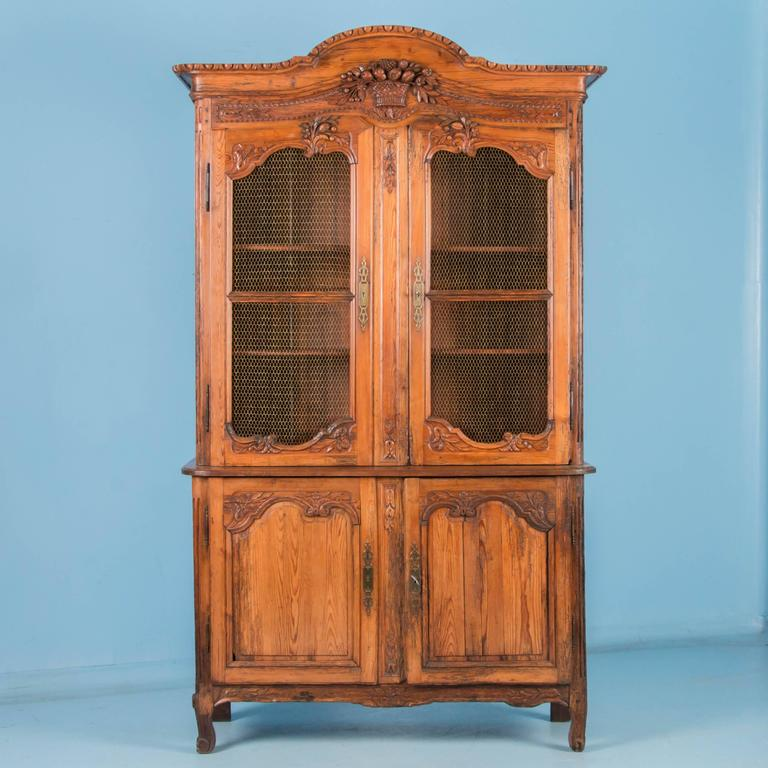 Antique hand-carved four door pine bookcase cabinet from France, circa 1820-1840, made in two sections with the upper doors covered in a honeycomb of brass wire. Elements of the carved woven basket with fruit and flowers in the crown, are repeated