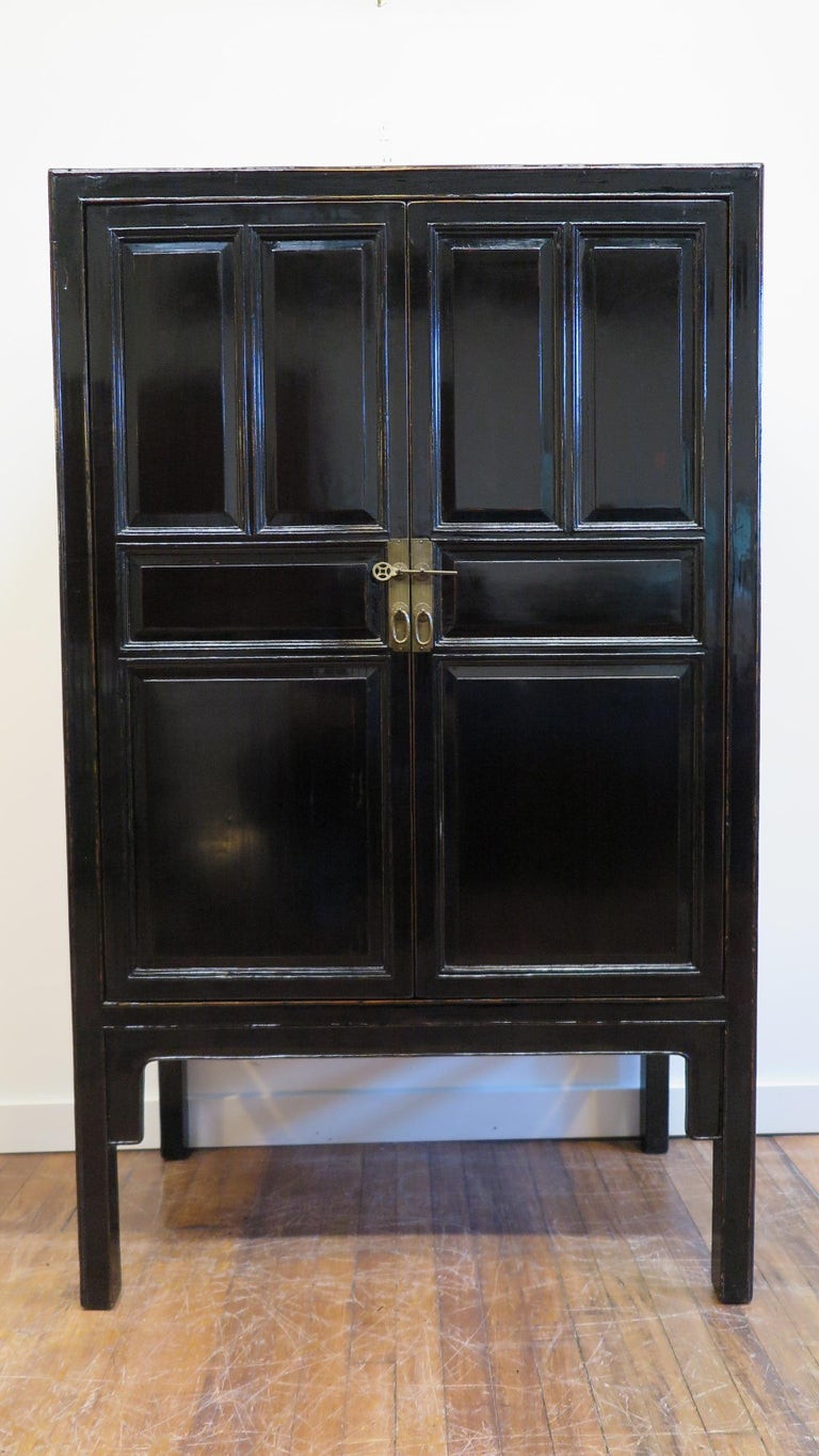 19th century Chinese black lacquer cabinet. A black lacquer Chinese scholars cabinet of cypress wood with black lacquer covering. In very fine condition, excellent, this 19th century Chinese panel cabinet has two drawers with two shelf's upper and