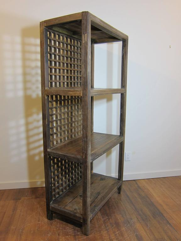 Antique rustic bookcase made of elm wood. Lattice style screened back. The elm wood is worn and faded, natural showing its age. In good condition. Wonderful piece.