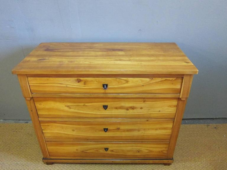 Period Biedermeier chest of drawers. Having four drawers, simple over hang detail to top frame on block feet. Cherry veneer over northern pine (pinotea), drawer fronts having buffalo horn escutcheons with working locks. Drawers exhibit plugged holes