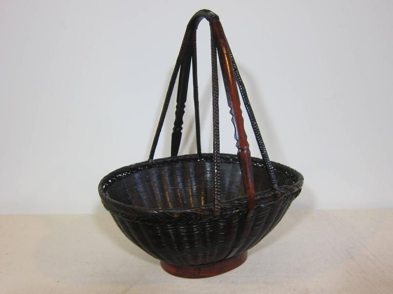 19th century antique woven basket. Decorative basket. This is an actual antique market basket in very good condition. Woven reed, bamboo, and wood. Having intricate detailed work, with carved handles.