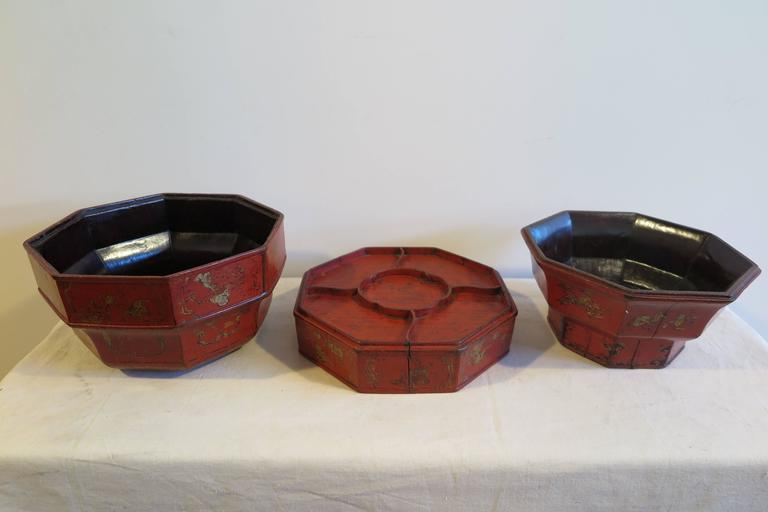 A 18th-19th century Chinese wooden octagon bowl box with gilt painting and red lacquer. Complex three part wooden serving bowl, tray, box. An early 19th century Qing Dynasty Imperial style fruit box. Having three serving pieces, two bowls and one