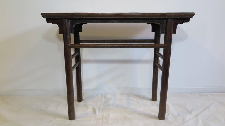 A 19th century Chinese console table, also referred to as a wine table. Original in excellent condition. Old growth Northern elmwood. Very solid. Having apron with spandrels, and uniform cylindrical round legs. This piece has a both a rustic appeal