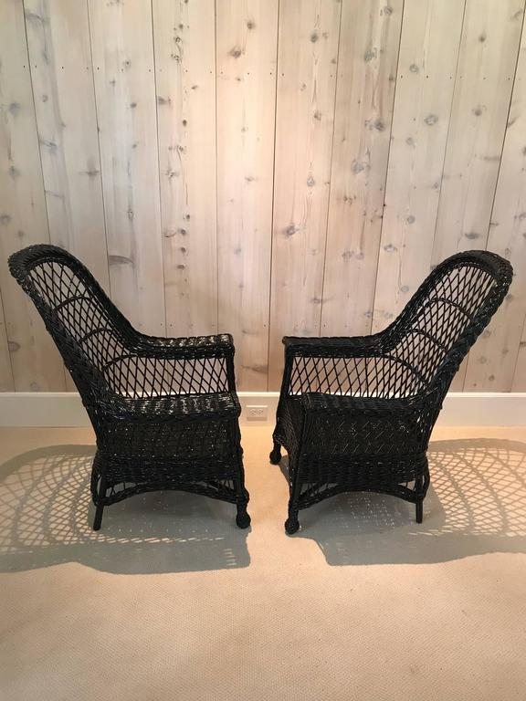 A pair of antique wicker chairs woven of willow by Paine Furniture in fresh black paint.