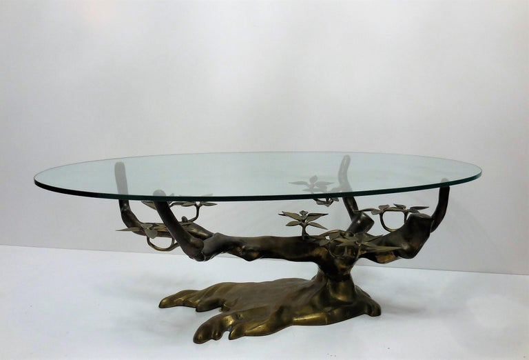 Spectacular table. A stylized version of a bonsai tree with an oval glass top. Beautiful age appropriate patina. Glass top measures 53