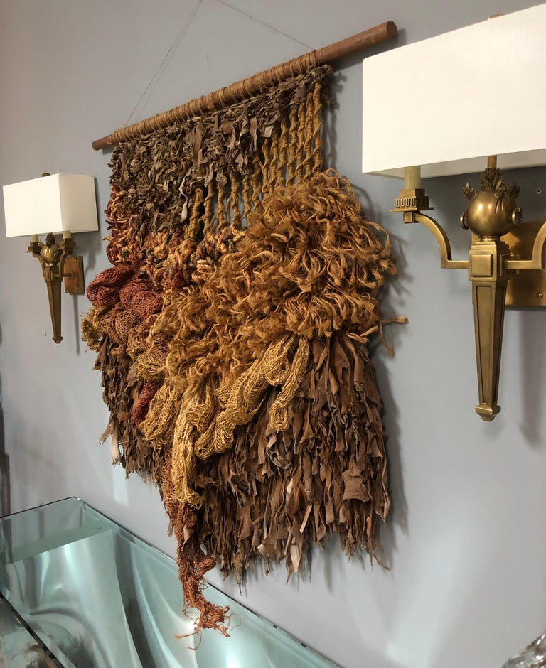 A highly textural leather and natural fibers wall sculpture. A wood rod holds the cascading creation that is made of pieces of leather and other natural fibers woven into the design.
