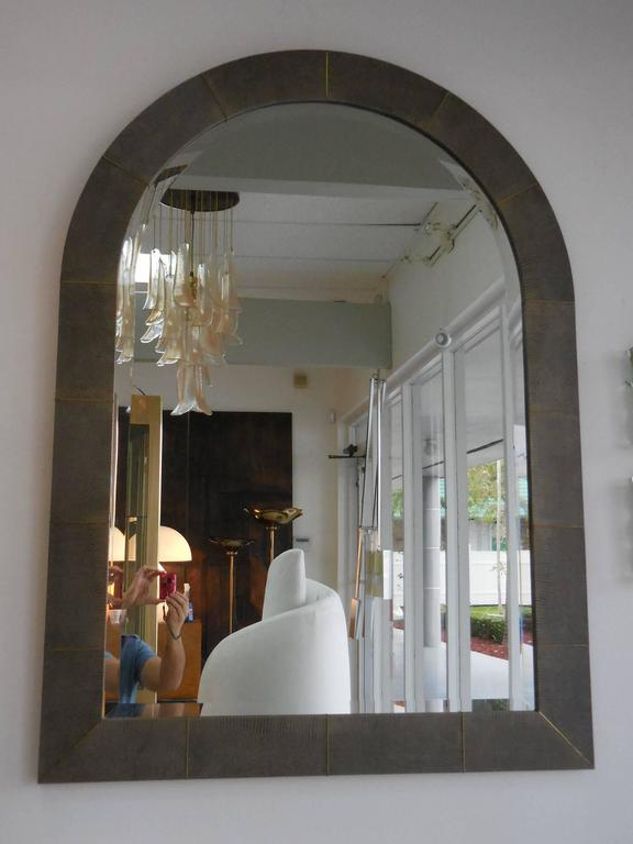 A large mirror by Karl Springer. Done in java lizard skin and brass inlay. Original bevelled mirror. Signed and dated on verso.