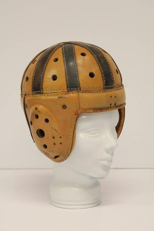 Antique Spalding football leather helmet with glass hat form.