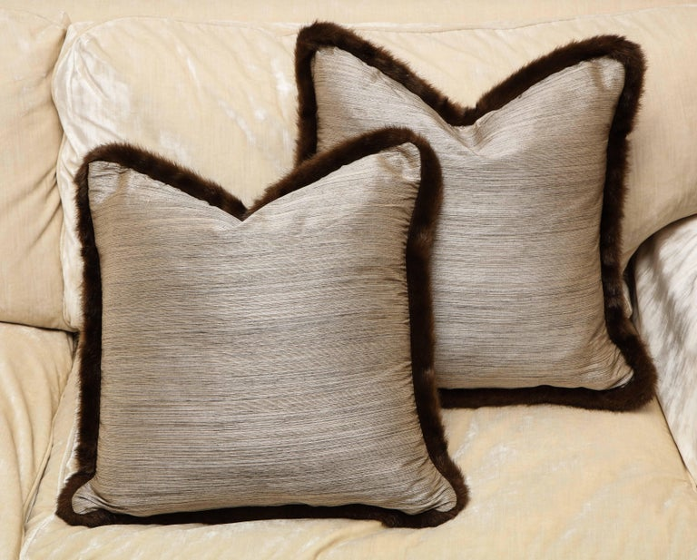 Chic and one of kind pair of silk and fur pillows. Silver and bronze textile with chestnut fur. The textile has Japanese English provenance from England, early 20th century. And the European fur around exudes Anglo-Japanese style. The pillow is