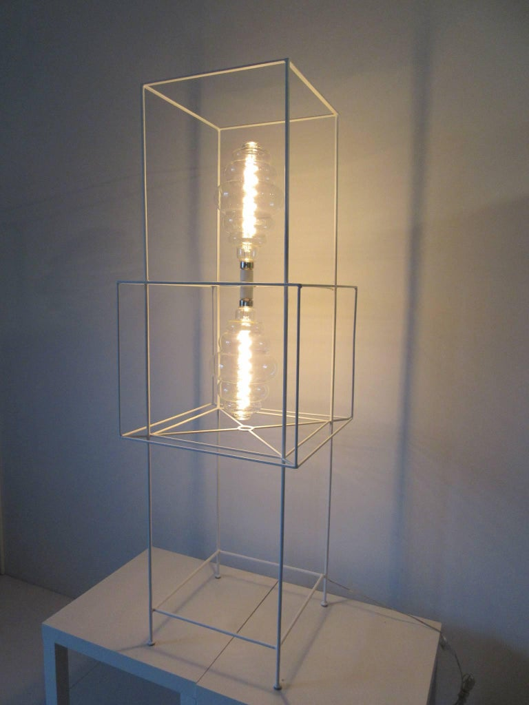A satin white iron floor lamp with boxed construction in a sculptured style with two LED hive styled light bulbs and floor foot switch, a great piece of art or lighting which works in many environments. Made in the manner of Frederick Weinberg with
