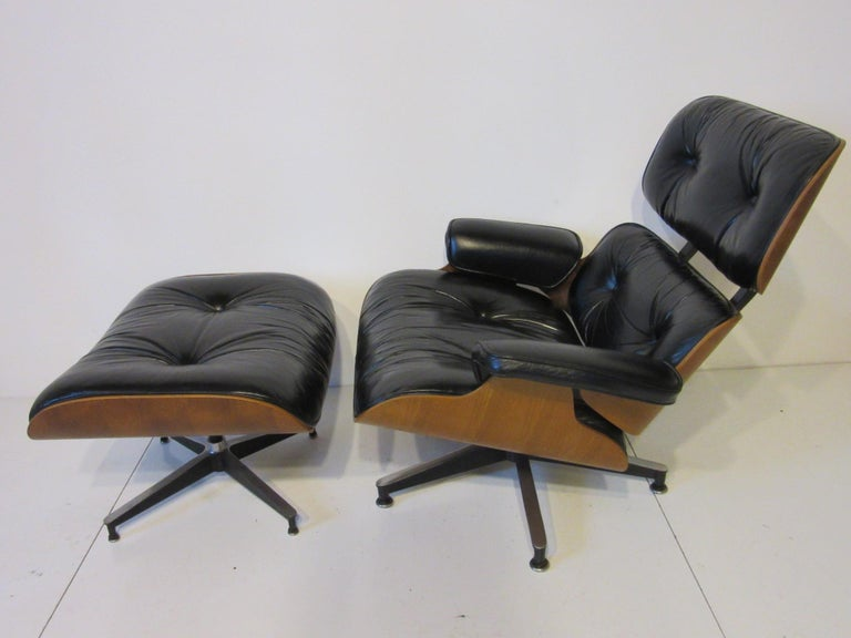 The classic iconic Eames lounge chair and ottoman with walnut frame, soft black leather upholstered cushions and cast aluminum legs. Retains the manufactures tags to each piece by the Herman Miller furniture company , measurement for the ottoman is