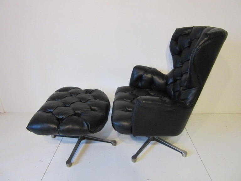 A lounge chair and matching ottoman in a very tight pebbled heavy black leatherette with tufted upholstery and cast aluminum swivelling bases. The chair itself has a spring to the bottom of the seat for rocking comfort, ottoman measurement is 26.25