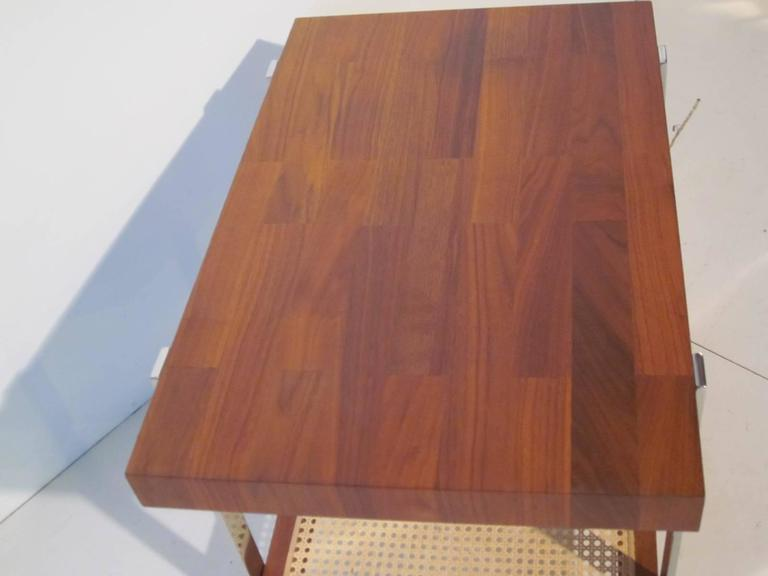 A walnut topped side table with chromed legs and lower storage shelve with cane insert in the style of Milo Baughman.
