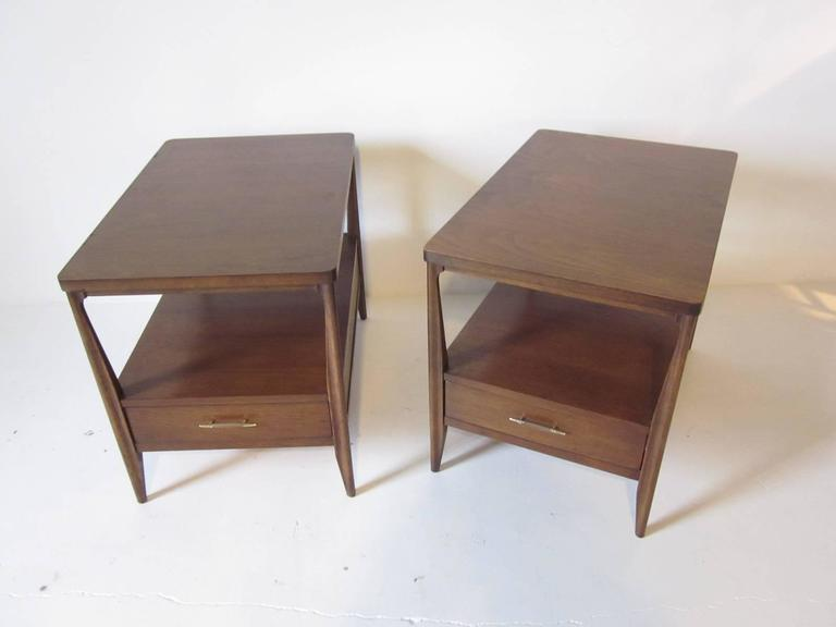 A pair of dark mahogany nightstands or end tables with lower single drawer, brass detailed wood pulls and tapered legs.