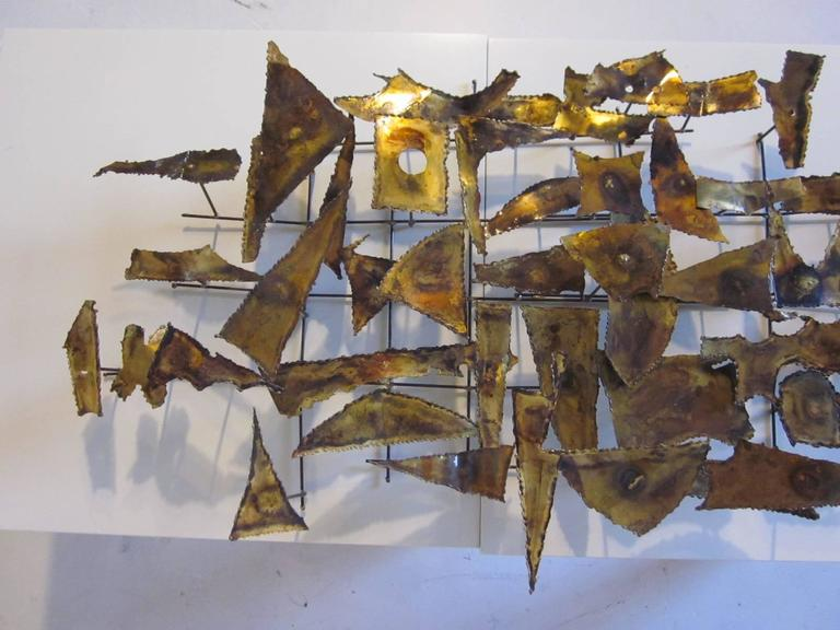 A Jere styled Brutalist brass, copper and torch cut wall sculpture with angled metal design.