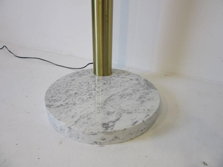 A six adjustable armed spray arc floor lamp with cylinder styled light fixtures, round white veined thick marble base and finished in a brushed brass with foot switch.