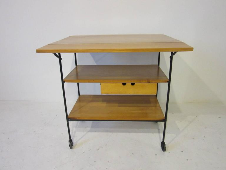 A maple wood bar or serving cart with two folding end pieces making a larger surface a small pull-out drawer on a satin black iron frame and wheels. From the planner group series for the Winchendon furniture company. Total measurement for the top