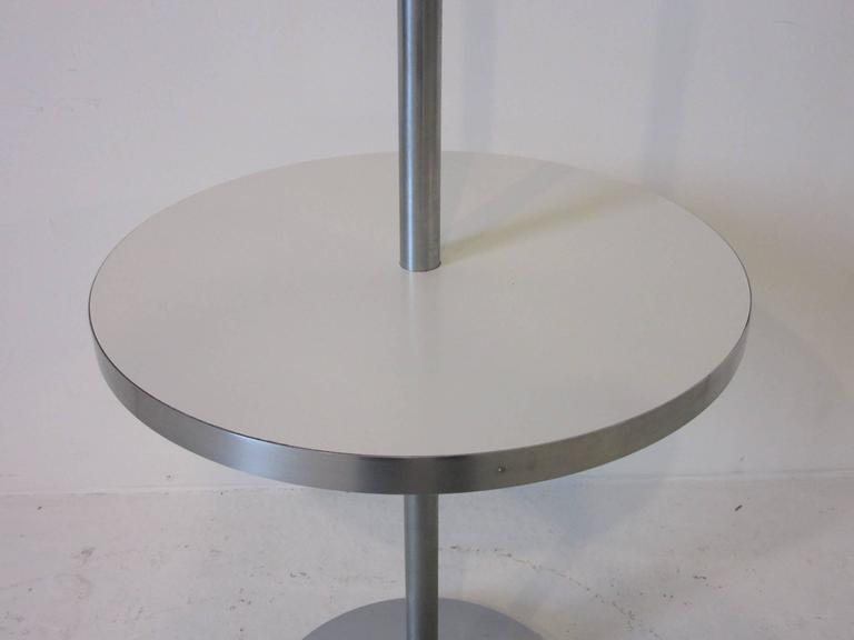 A brushed stainless steel pole floor lamp with integrated laminate drink table with metal base and original linen shade. Manufactured by the Nessen Lamp Company. The drink table measurement is 14