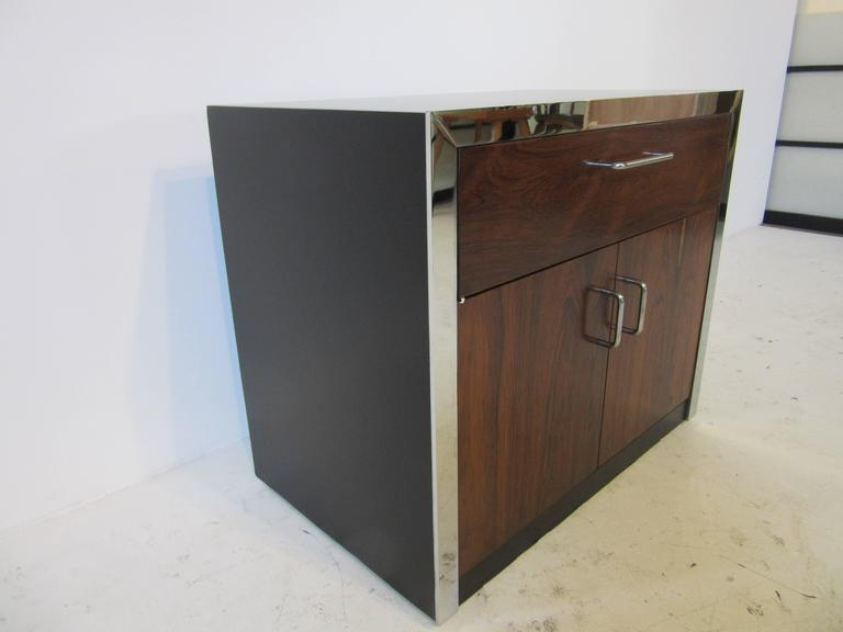 A 1970s Brazilian rosewood nightstand with top drawer and lower double doors with storage. Detail chrome trim surrounds the front with a satin black wood cabinet and chrome pulls. Designed in the style of Milo Baughman.