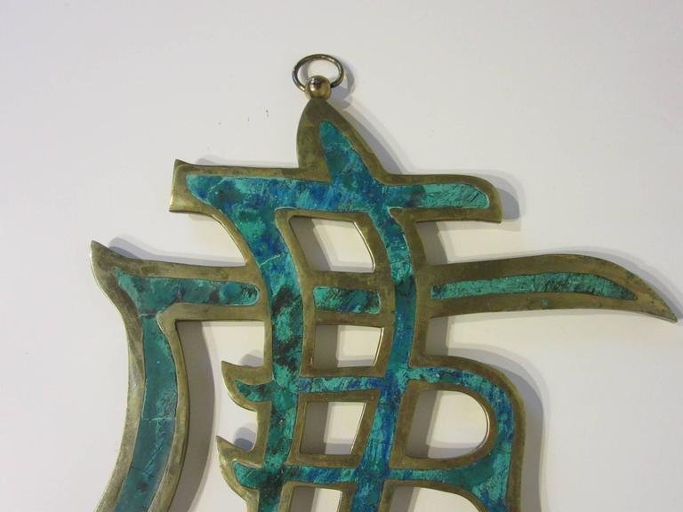 A brass and malachite handcrafted hanging wall ornament with inlay stone, hanger and retains the label