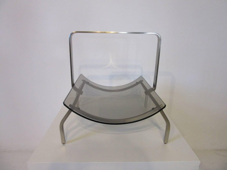 A stainless steel sculptural framed magazine rack with curved smoked glass insert made in Italy by Fontana Arte .
