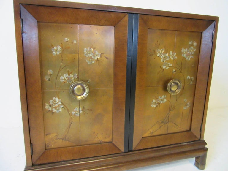 A decorated double door commode or cabinet with gold leaf and painted front, mahogany and black detailed chest with brass pulls and feet caps. Made by the Johnson Brothers Furniture Company.