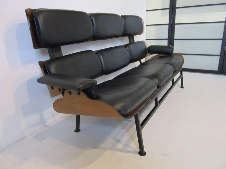 A rare Plycraft pre-production working prototype in the style of the lounge chairs, used in designing and researching the idea for a new type of sofa. Constructed of molded walnut wood with button attached leatherette cushions and a stain black